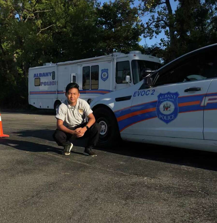 Francis HungMang poses next to an Albany police car.