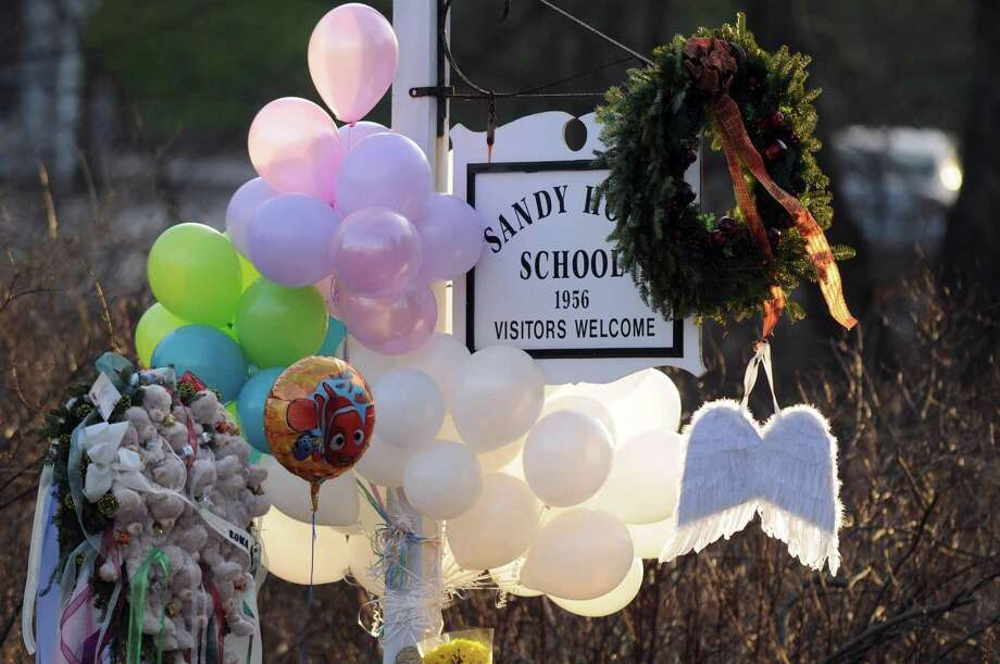In this 2012 file photo, flowers, teddy bears, candles, balloons and a pair of angel wings left by mourners are seen at the Sandy Hook Elementary School sign. Photo: File Photo / Hartford Courant