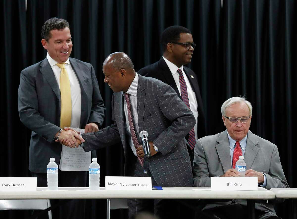 Tony Buzbee greets Mayor Sylvester Turner, as Bill King sits to the right, during a candidate forum for the 2019 election at the Garden Oaks Montessori Magnet school, September 3, 2019, in Houston.