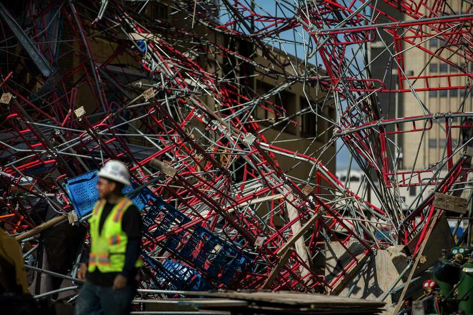Construction workers begin cleaning up collapsed scaffolding on the 300 block of East Martin Street in San Antonio on Friday, Sept. 20, 2019. High winds from last night's storm caused the scaffolding to fall from the side of the former AT&T building and land on the St. MarkÕs Episcopal Church across the street. Photo: Daniel Carde, Special Contributor / Daniel Carde