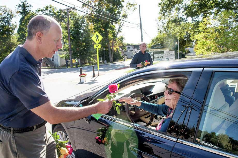 John DiCenzo hands out a rose as part of the Wilton Chamber of Commerc's Random Acts of Kindness day on Friday, Sept. 20. Photo: Bryan Haeffele / Hearst Connecticut Media / Hearst Connecticut Media