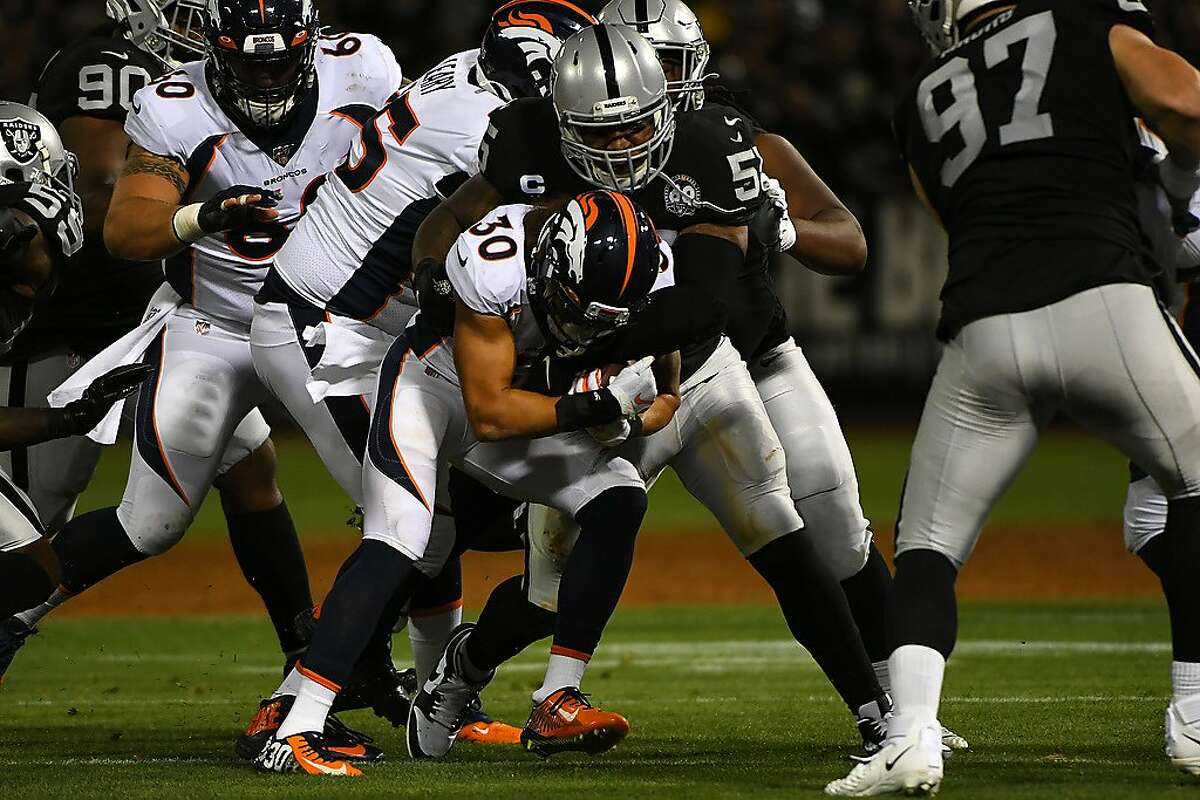 OAKLAND, CALIFORNIA - SEPTEMBER 09: Phillip Lindsay #30 of the Denver Broncos is tackled by Vontaze Burfict #55 of the Oakland Raiders during their NFL game at RingCentral Coliseum on September 09, 2019 in Oakland, California. (Photo by Robert Reiners/Getty Images)