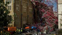 Construction workers begin cleaning up collapsed scaffolding Friday on the 300 block of East Martin Street.