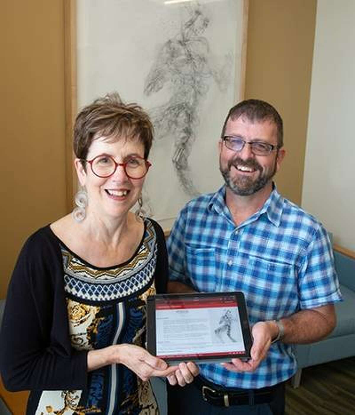 University Museum Executive Curator Erin Vigneau-Dimick, left, and Associate Professor Dave Jennings display their AISLE project showing people the scientific connection of selected artwork installed throughout SIUE's Science West and Science East. Arboreal Anatomy by professor Brigham Dimick is featured in the background.