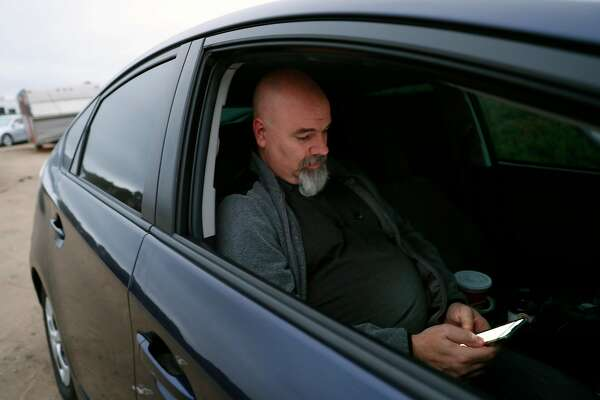 Uber driver Gary Branson sits in the passenger seat as he readies to sleep in his vehicle in San Francisco, Calif., on Sunday, August 18, 2019.