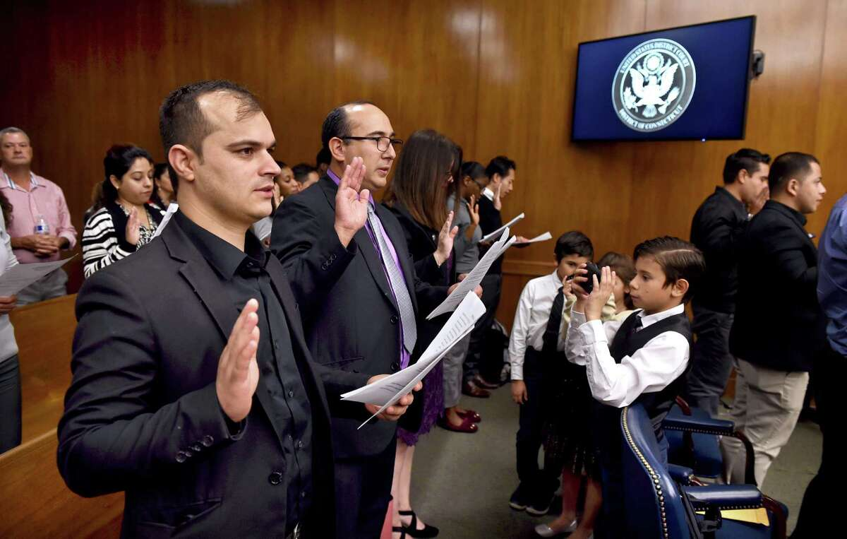 Bashir Safi, left, recites the Oath of Allegiance during a naturalization ceremony at U.S. District Court in Bridgeport on Sept. 18, 2019, 10 years after coming to this country as a refugee from Afghanistan.