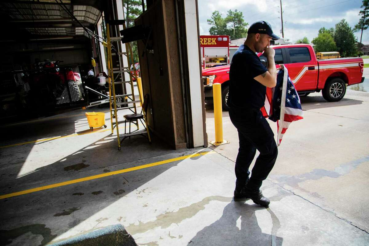 Caney Creek Fire Department firefighter Luke Hancock, 24, walks out of the flooded fire station on Friday, Sept. 20, 2019, in Conroe holding a United States flag to attach it to a pole and raise it in front of the station. The fire station he works at, got flooded on Thursday.