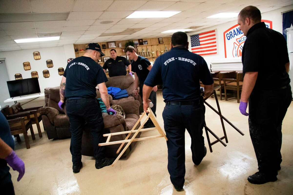 Caney Creek Fire Department firefighters move furniture from water damaged rooms on Friday, Sept. 20, 2019, in Conroe, after their fire station got flooded on Thursday.