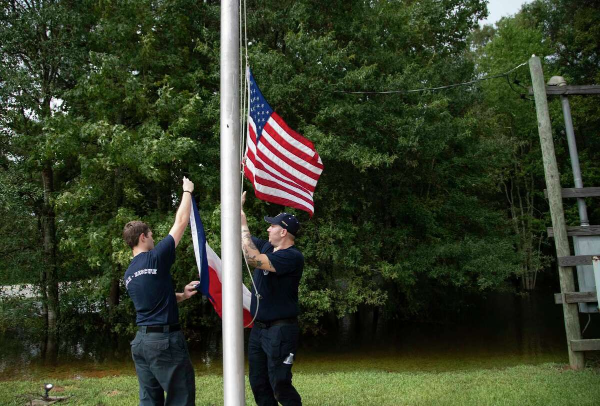 Caney Creek Fire Department firefighters Avery Aultman, 21, left, Luke Hancock, 24, right, raise the United States flag and the Texan flag while cleaning up the fire station on Friday, Sept. 20, 2019, in Conroe after it got flooded on Thursday.