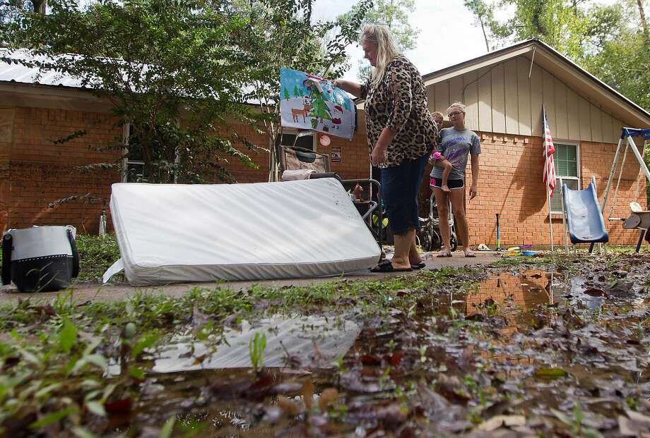 Linda Mason carries possessions at her home in Splendora, Texas, after it was flooded with 3.5 feet of water from the remnants of Tropical Storm Imelda. Floodwaters began to recede Friday. Photo: Jason Fochtman / Houston Chronicle