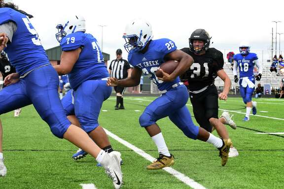 Cy Creek senior running back Jaydon Gilbert (26) runs for yardage against the Richmond Foster defense during their three-way scrimmage in preseason.