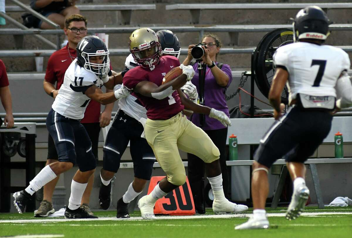 Cy Woods senior running back Christian Scott, center, fights to stay in bounds against Tomball Memorial defenders Josh Ruiz (17) and Anthony Jones (behind Scott) in the 1st quarter of their matchup with Cy Woods at Pridgeon Stadium in Cypress on Friday, Sept. 13, 2019.
