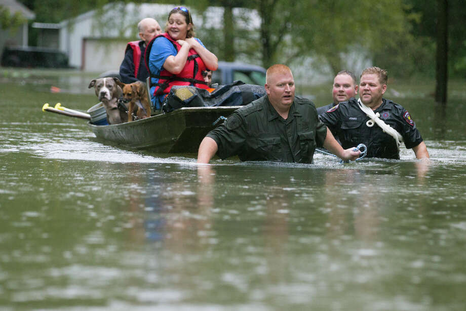 Splendora Police Lt. Troy Teller, left, Cpl. Jacob Rutherford and Mike Jones pull a boat carrying Anita McFadden and Fred Stewart from their flooded neighborhood inundated by rains from Tropical Depression Imelda on Thursday, Sept. 19, 2019, in Spendora. Photo: Brett Coomer/Staff Photographer / © 2019 Houston Chronicle