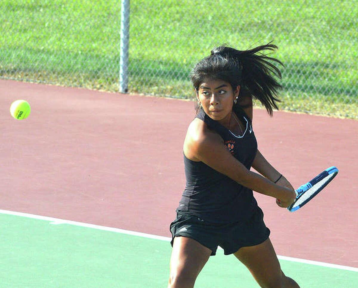 Edwardsville junior Chloe Trimpe makes a backhand return during her No. 2 doubles match against Belleville East on Thursday at the EHS Tennis Center.