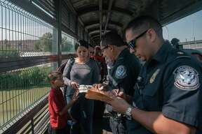 FILE-- U.S. Customs and Border Patrol officials check the papers of a Venezuelan family asking for asylum on the international bridge between Laredo, Texas, and Nuevo Laredo, Mexico, July 10, 2019. The U.S. Supreme Court on Sept. allowed the Trump administration to bar many Central American migrants from seeking asylum in the U.S. The court said the administration may enforce new rules that generally forbid asylum applications from people who had traveled through another country on their way to the United States without being denied asylum in that country. (Luis Antonio Rojas/The New York Times)