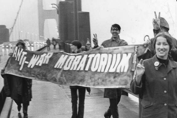 Anti war protestors carry signs as they march across the Golden Gate Bridge on Moratorium Day,  October 15, 1969  Photo ran 10/16/1969, p. 6