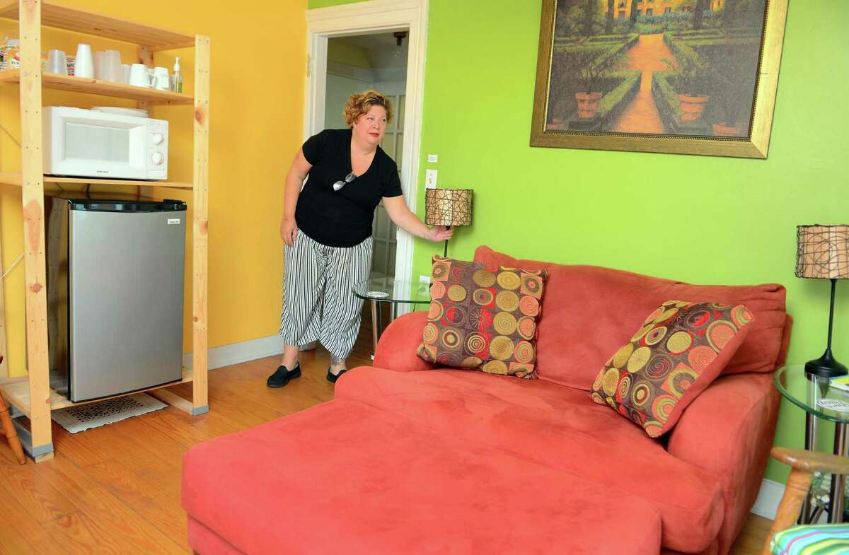 Juliet Novak shows one of the upstairs rooms she rents out for short-term stays.