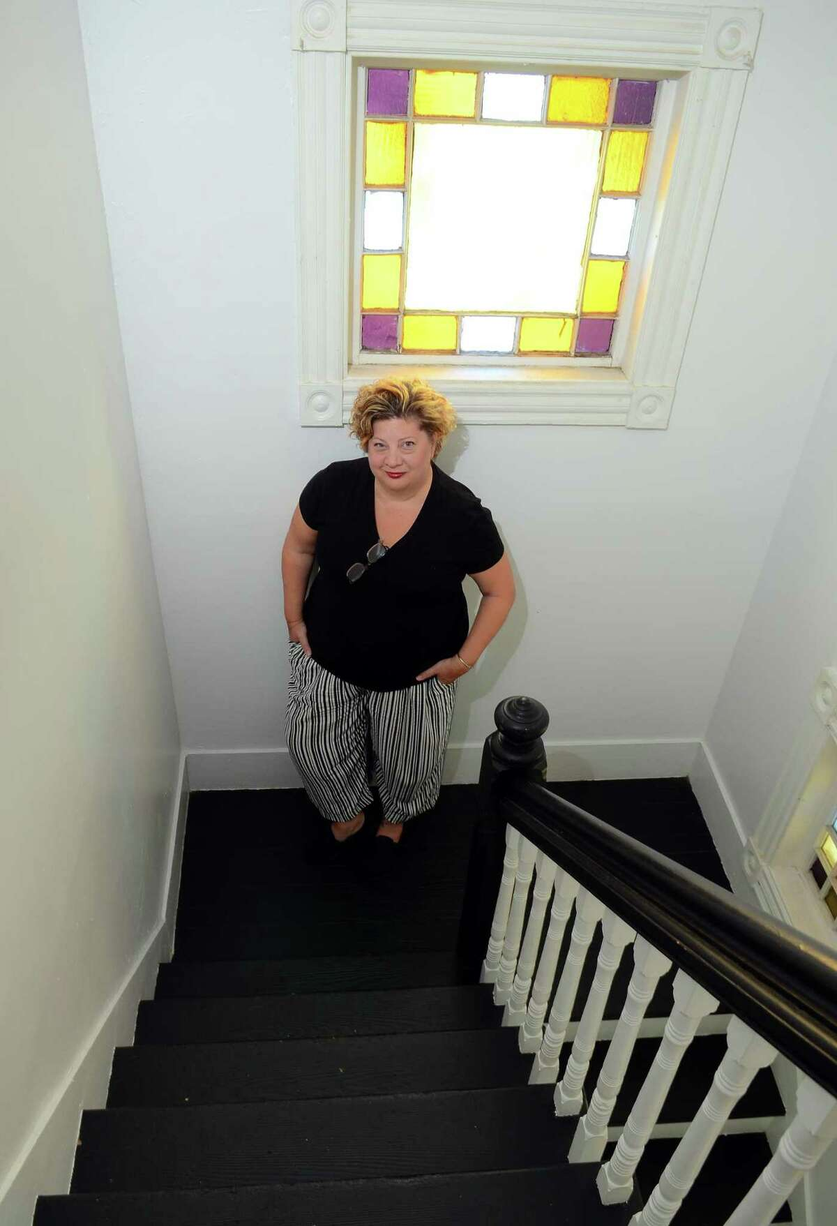 Juliet Novak poses at her home in West Haven, where she has rented space for short-term stays.