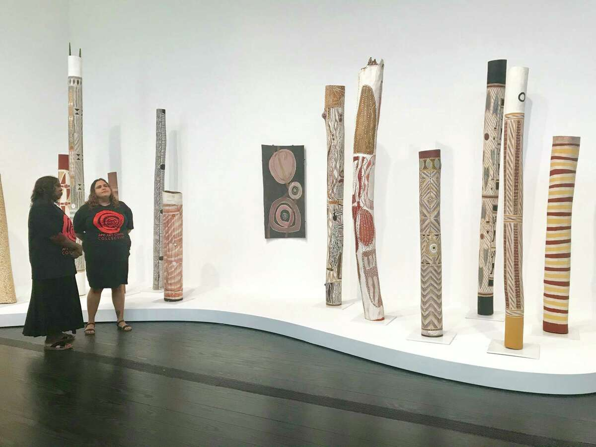 """Artist Teresa Baker, left, and Sally Scales, both from Australia's Anangu Pitjantjatjara Yankunytjatjara (APY) Lands, view hollow-log-coffin sculptures in the exhibition """"Mapa Wiya (Your Map's Not Needed)."""""""