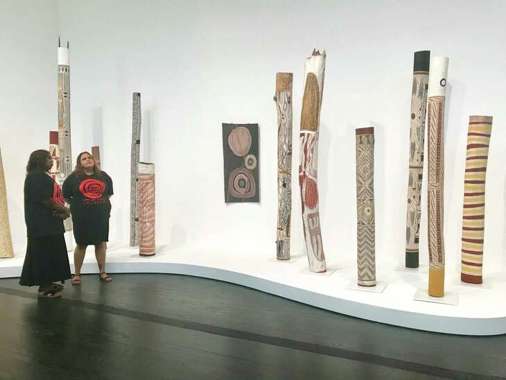 "Artist Teresa Baker, left, and Sally Scales, both from Australia's APY Lands, view hollow-log-coffin sculptures within the exhibition ""Mapa Wiya (Your Map's Not Needed)."""