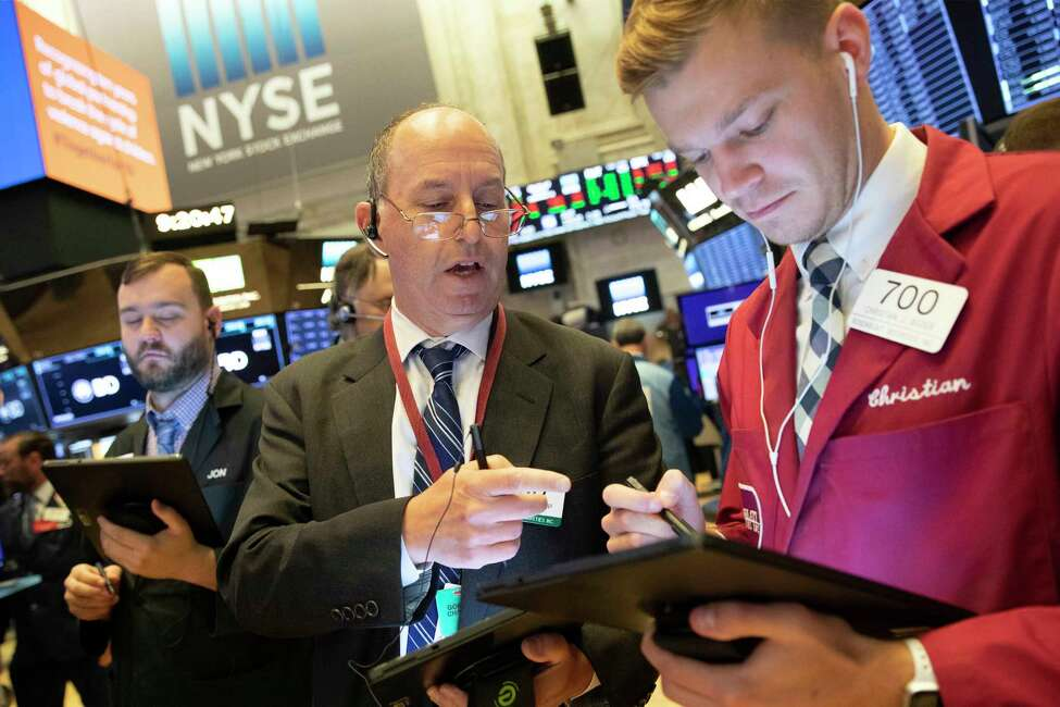 FILE - In this Sept. 16, 2019, file photo Gordon Charlop, center, and Christian Bader work at the New York Stock Exchange. The U.S. stock market opens at 9:30 a.m. EDT on Friday, Sept. 20. (AP Photo/Mark Lennihan, File)