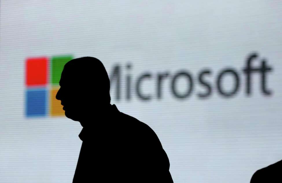 FILE - In this Nov. 7, 2017, file photo, an unidentified man is silhouetted as he walks in front of Microsoft logo at an event in New Delhi, India. Shares of Microsoft hit an all-time high after the tech giant announced a big hike in its dividend and a stock buyback plan. Late Wednesday, Sept. 18, 2019, the Redmond, Washington-based company announced that its board approved a plan to repurchase up to $40 billion in stock. (AP Photo/Altaf Qadri, File)
