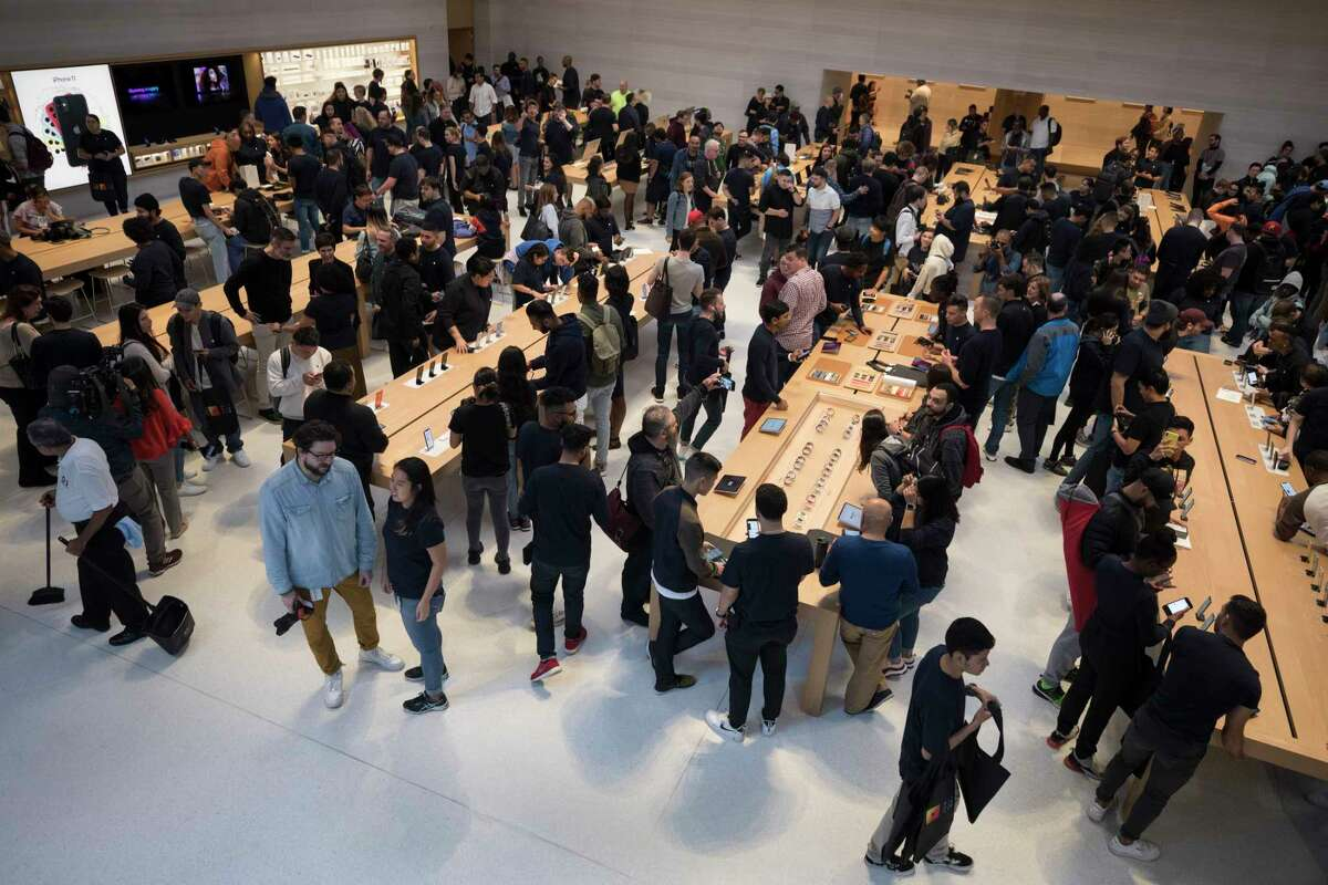 Shoppers inspect Apple products at their New York store on Friday, Sept. 20, 2019. The iPhone 11 became available Friday. (James Estrin/The New York Times)