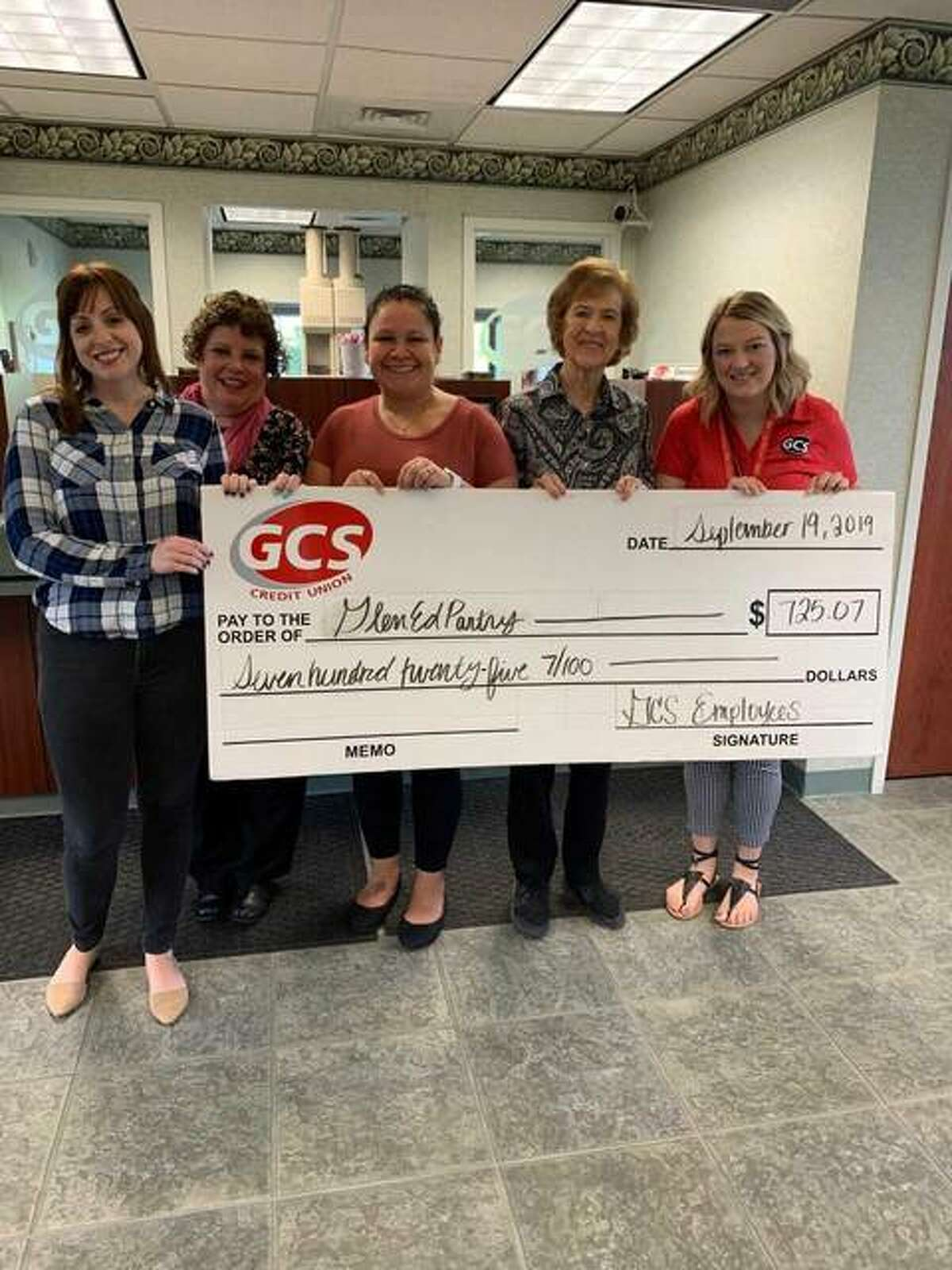 GCS Credit Union employees donate a check for roughly $725 to Glen-Ed Pantry representatives.