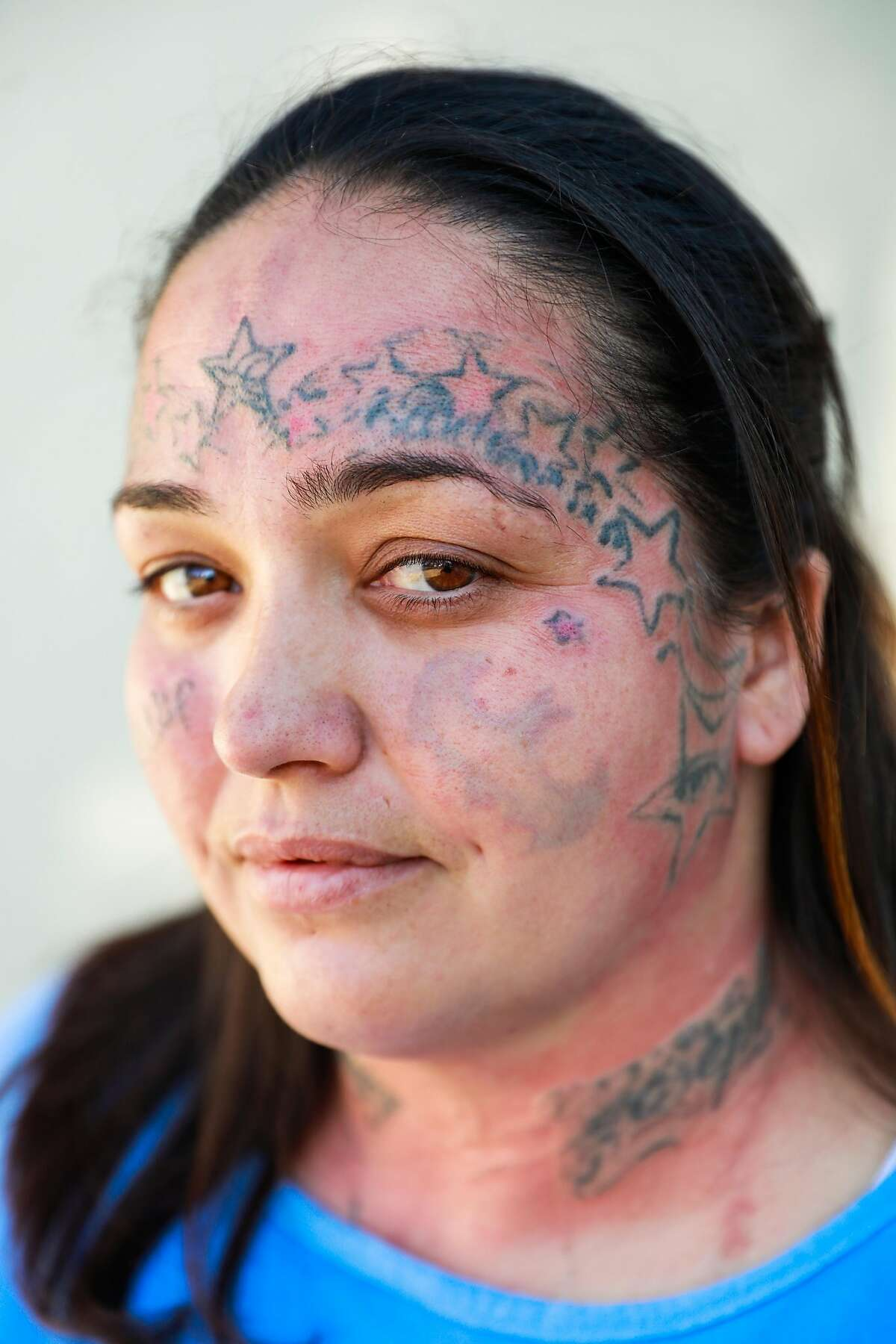 April Diaz, 36, stands for a portrait moments after a tattoo laser removal treatment for all of the tattoo's on her face at the Folsom women's facility at the Folsom state prison in Folsom, California, on Friday, Sept. 13, 2019. April said her dad gave her her first tattoo at age 15.