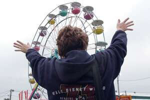 Jane Solomine of East Haven waves to her husband and children riding on the Ferris wheel at the Durham Fair in this September 2003 archive shot.