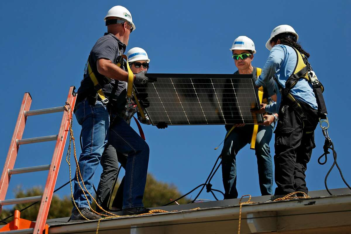 (left to right) Steve Buster, Lauren Krause, Marvin Dizon and Luis Chavez install a solar panel in Richmond, Calif., on Wednesday, September 11, 2019, as part of a non-profit venture to provide solar power to residential homes.