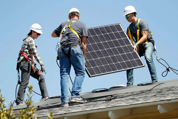 (left to right)  Lauren Krause, Steve Buster and Marvin Dizon install a solar panel in Richmond, Calif., on Wednesday, September 11, 2019, as part of a non-profit venture to provide solar power to residential homes.