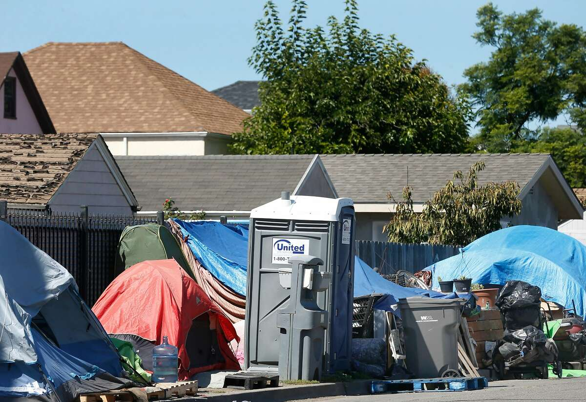 A homeless encampment equipped with portable toilets is set up on Bond Street between High Street and 42nd Avenue, directly behind a row of houses, in Oakland, Calif. on Friday, Sept. 20, 2019.