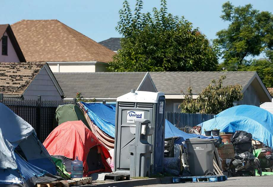 A homeless encampment equipped with portable toilets is set up on Bond Street between High Street and 42nd Avenue, directly behind a row of houses, in Oakland, Calif. on Friday, Sept. 20, 2019. Photo: Paul Chinn / The Chronicle