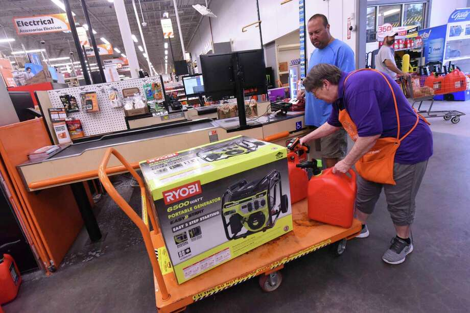 FILE - In this Sept. 2, 2019, file photo Delma Hewitt checks out Al Lombardi as he purchases a new generator and other supplies at the Home Depot in Monkey Junction, N.C. Backup power options range from gasoline-powered portable generators, which can cost $1,000 or more, to solar panels plus batteries, which cost tens of thousands of dollars to purchase and install. (Ken Blevins/The Star-News via AP, File) Photo: Ken Blevins / The Star-News