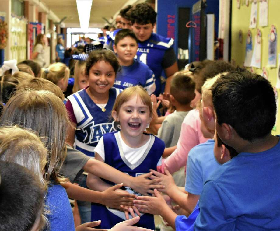 Proudly in the lead as Needville Blue Jay football players make their way through the halls of the elementary school on game day last Friday is kindergarten student Merritt Russell. Behind her are fellow Needville Elementary students Vanessa Alonzo, Stormy Albright and George Munoz, and varsity player Chris Hein, all receiving high fives and good luck wishes from the elementary school students. Photo: Needville ISD / Needville ISD
