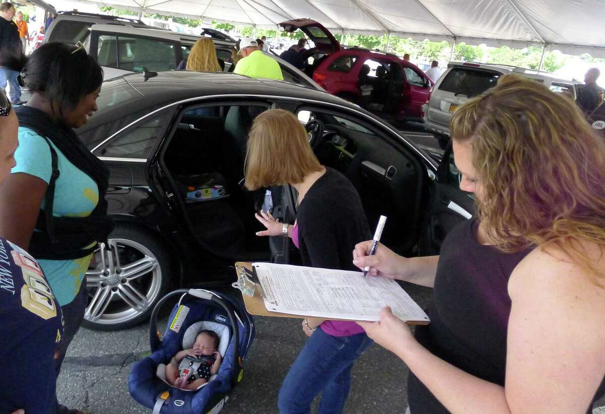 Tia Olds, left, with her three-week-old daughter Erin Leach get assisted my child seat safety technicians Heather Falice and Jessica Baird of Parsons Child & Family Center during the Albany County 15th annual child safety seat check at Colonie Center in Colonie N.Y. Friday June 8, 2012. (Michael P. Farrell/Times Union)