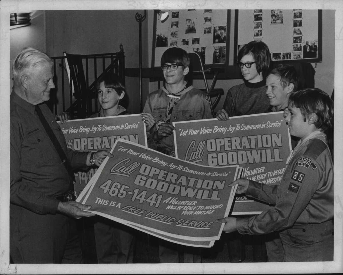 Operation Goodwill. Boy Scout Troop 85, Elsmere, New York, boys hold Operation Goodwill signs at the Wellington Hotel, Albany, NY. Frank R Eyre, Scoutmaster, with scouts David Howell, 11, Weston Greenmoor, 13, Ansel Groore, 11, Larry Lonzo, 13 and Jim Howell, 12. December 7, 1971 (Bob Wilder/Times Union Archive)