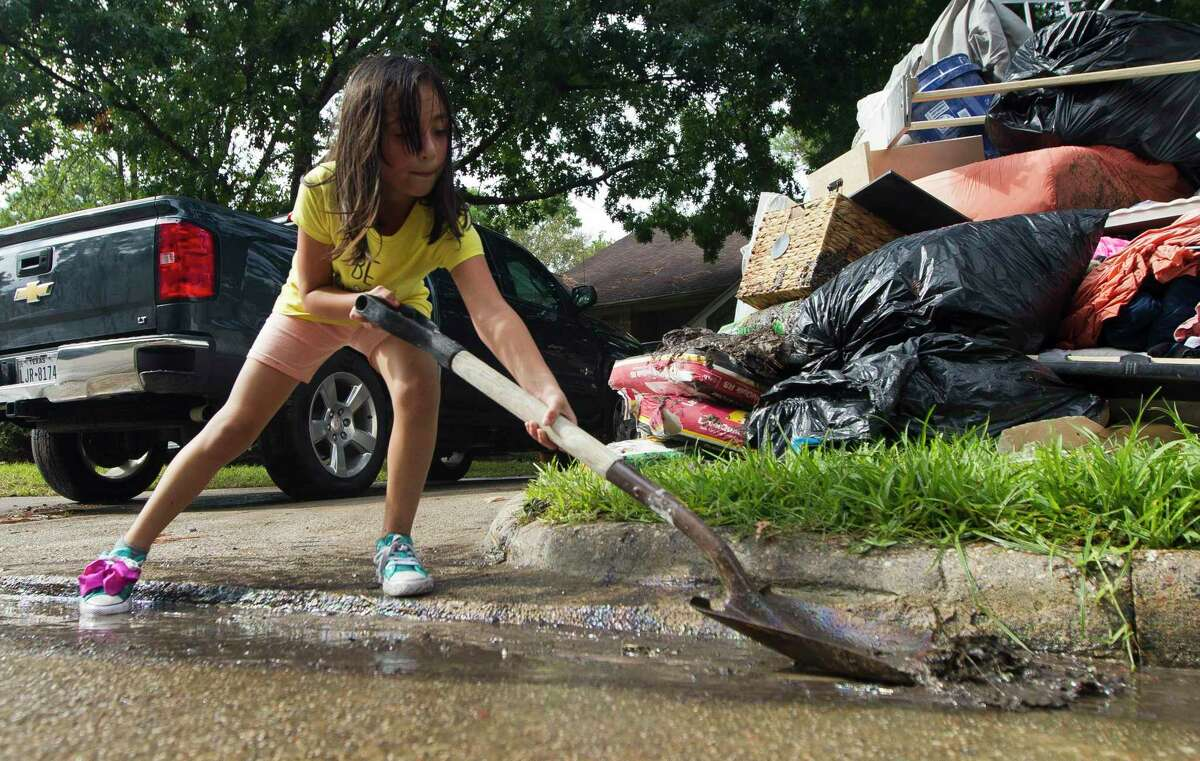 Angeleen Garza helps move floodwater and debris infront of their home in the Elm Grove subdivision toward a nearby storm drain, Friday, Sept. 20, 2019, in Kingwood.
