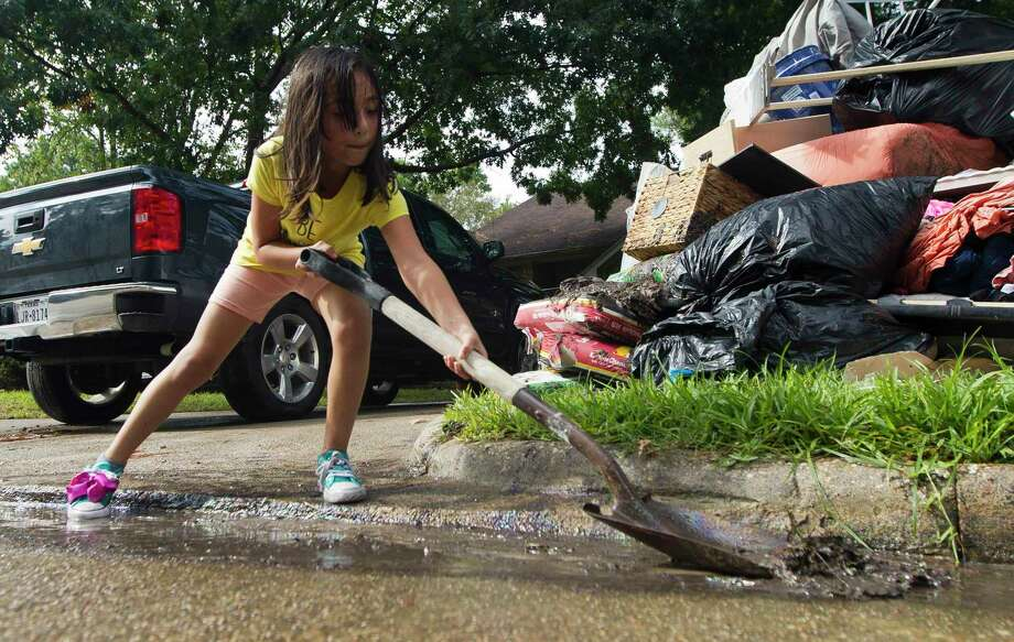 Angeleen Garza helps move floodwater and debris infront of their home in the Elm Grove subdivision toward a nearby storm drain, Friday, Sept. 20, 2019, in Kingwood. Photo: Jason Fochtman, Houston Chronicle / Staff Photographer / Houston Chronicle