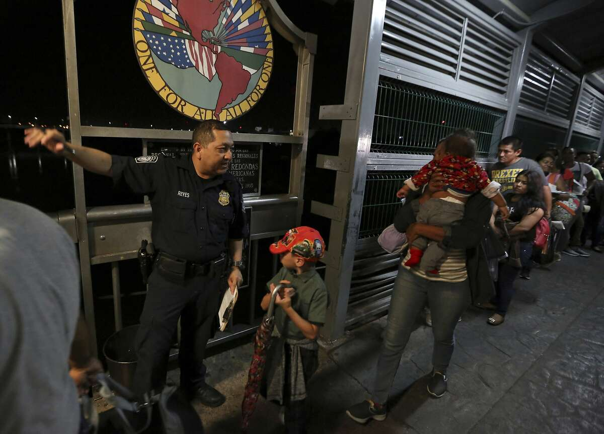 A U.S. Customs and Border Protection officer gives instructions to migrants who are on their way to apply for asylum in the United States, on International Bridge 1 as they depart Nuevo Laredo, Mexico, early Tuesday, Sept. 17, 2019. Tent courtrooms opened Monday in two Texas border cities to help process thousands of migrants who are being forced by the Trump administration to wait in Mexico while their requests for asylum wind through clogged immigration courts. (AP Photo/Fernando Llano)