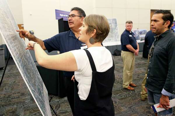 CPS representative Juan Sandoval locates an address as concerned citizens attend a CPS open house concerning the proposed Midtown Substation and Transmission Project at Temple Beth-El on Sept. 19, 2019. Homeowners Lizzie Pearson and Araiza look over the map of the area in question.
