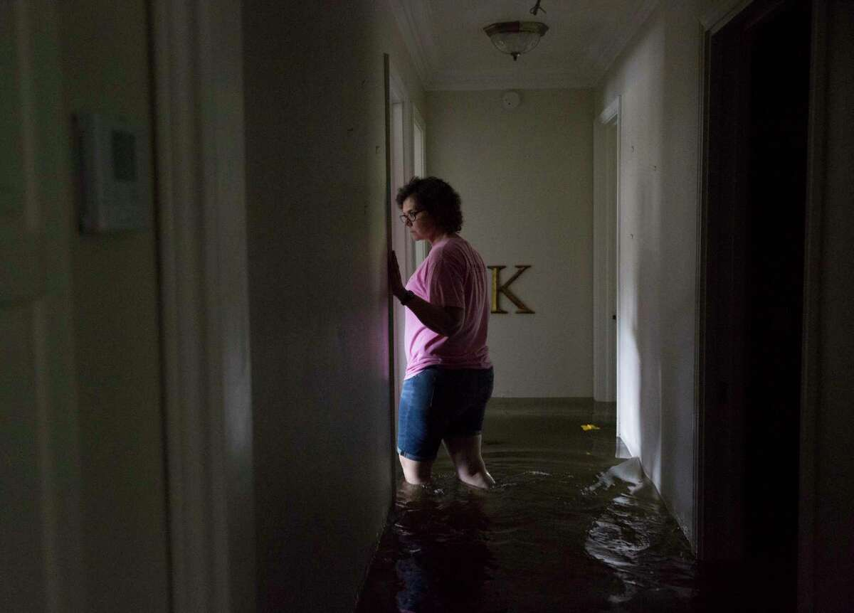 Jennifer Hoelscher, of Spring, goes through her mother's flooded house in Teacherville neighborhood on Franzen Road on Friday, Sept. 20, 2019, in Winnie. While water has gone down in many plaes, many houses on Franzen Road were will under water.