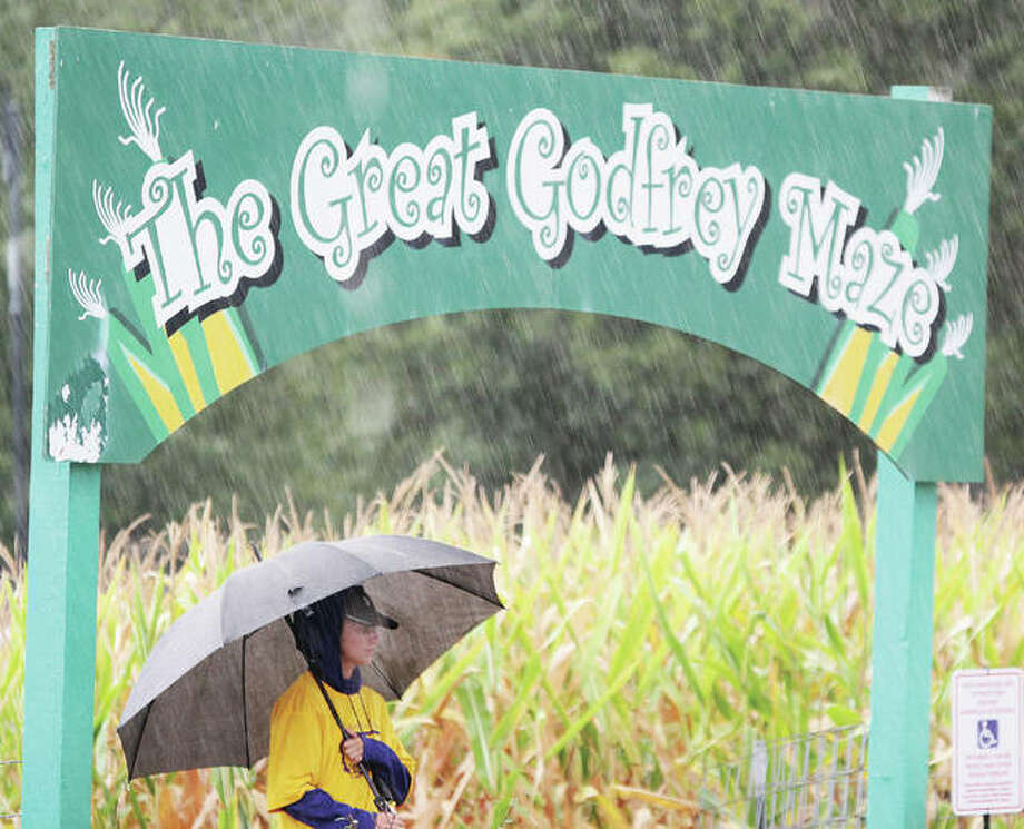 A wet Eva Schwaab watches over the entrance to the Great Godfrey Maze, which opened Friday. Rain hit just after the maze opened, making for sparse crowds. The maze will be open weekends through Nov. 3.