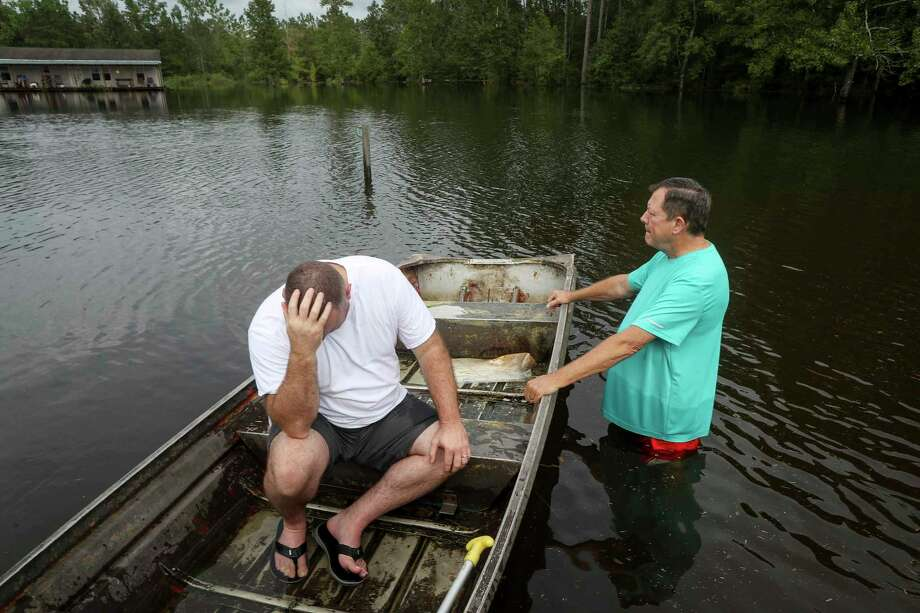 "Stephen Gilbert, left, and his father-in-law sit in front of their flooded property on Friday, Sept. 20, 2019, in the Mauriceville, Texas, area. Floodwaters are starting to recede in most of the Houston area after the remnants of Tropical Storm Imelda flooded parts of Texas. ""I'm on my third house,"" said Gilbert, who lives behind his father-in-law. ""I wouldn't go anywhere else in the world,"" he said. ""All we have is family anyway."" ( Jon Shapley/Houston Chronicle via AP) Photo: Jon Shapley, Associated Press / © 2019 Houston Chronicle"