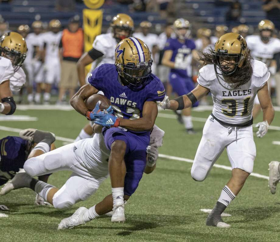 Midland High's Daniel Garcia (32) is tackled by Abilene High's Ryan Cruz and Jorge Hernandez (31) on Friday, Sept. 20, 2019 at Grande Communications Stadium. Photo: Jacy Lewis/Reporter-Telegram