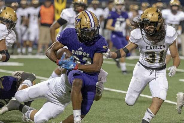 Midland High's Daniel Garcia (32) is tackled by Abilene High's Ryan Cruz and Jorge Hernandez (31) on Friday, Sept. 20, 2019 at Grande Communications Stadium.