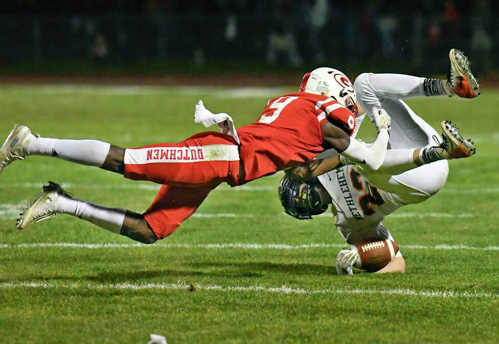 Guilderland's Brady Igweike (9) tackles Bethlehem's Nick Gicewicz (22) during a Section II Class AA boys' high school football game in Guilderland, N.Y., Friday, Sept. 20, 2019. (Hans Pennink / Special to the Times Union)
