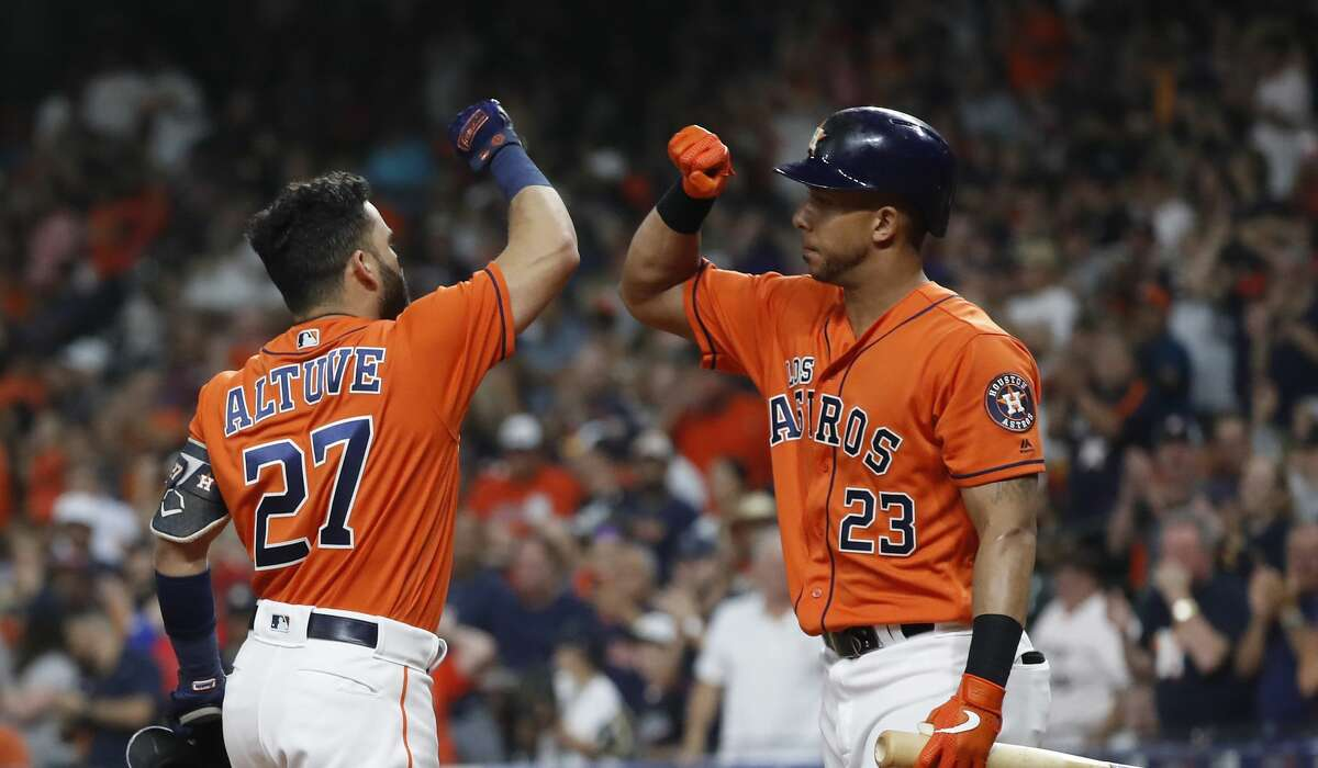 Houston Astros Jose Altuve (27) celebrates his home run with Michael Brantley (23) during the first inning of an MLB baseball game at Minute Maid Park, Friday, Sept. 20, 2019, in Houston.