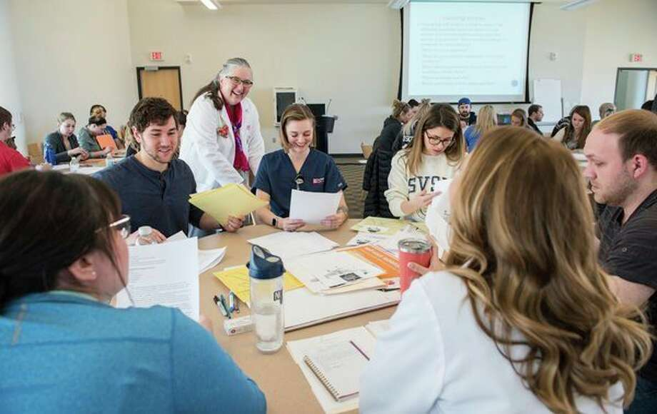 """Andrea Frederick, SVSU associate professor of nursing, works with students in class. SVSU recently was designated a """"Great College to Work For"""" in part for its excellent teaching environment. (Photo provided/ Tim Inman, SVSU)"""